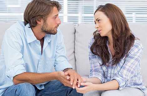 Couples sitting on sofa discussing with counselor